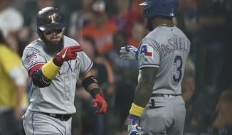 Texas Rangers Rougned Odor, left, motions to Delino DeShields after hitting a three-run home run against the Baltimore Orioles in the first inning of a baseball game, Saturday, Sept. 7, 2019, in Baltimore. (AP Photo/Gail Burton)