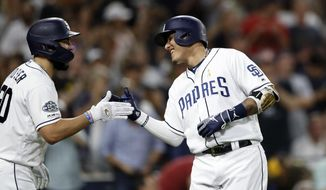 San Diego Padres' Manny Machado, right, reacts with teammate Eric Hosmer after hitting a two-run home run during the sixth inning of a baseball game against the Colorado Rockies, Saturday, Sept. 7, 2019, in San Diego. (AP Photo/Gregory Bull)