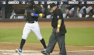 Miami Marlins' Jorge Alfaro scores as home plate umpire Marvin Hudson watches after Caleb Smith was hit by a pitch with the bases loaded during the second inning of a baseball game against the Kansas City Royals, Saturday, Sept. 7, 2019, in Miami. (AP Photo/Wilfredo Lee)
