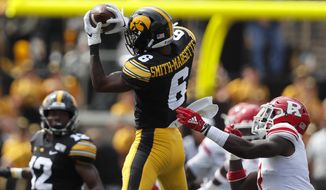 Iowa wide receiver Ihmir Smith-Marsette, center, makes a reception for the first down as Rutgers defensive back Avery Young, right, defends during the first half of an NCAA college football game, Saturday, Sept. 7, 2019, in Iowa City. (AP Photo/Matthew Putney)