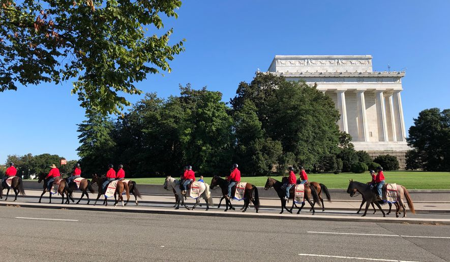 Military veterans participating in the Trail to Zero campaign ride horseback through Washington, D.C., on Sept. 7, 2019. The ride's goal is to raise awareness about how equine therapy can help veterans suffering from combat-related PTSD. (Shen Wu Tan/The Washington Times)