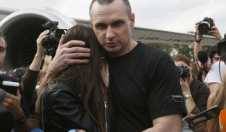 Ukrainian filmmaker Oleg Sentsov hugs his daughter upon his arrival at Boryspil airport, outside Kyiv, Ukraine, Saturday, Sept. 7, 2019. Planes carrying prisoners freed by Russia and Ukraine have landed in the countries' capitals, in an exchange that could be a significant step toward improving relations between Moscow and Kyiv. The planes, each reportedly carrying 35 prisoners, landed almost simultaneously at Vnukovo airport in Moscow and at Kyiv's Boryspil airport. (AP Photo/Efrem Lukatsky)