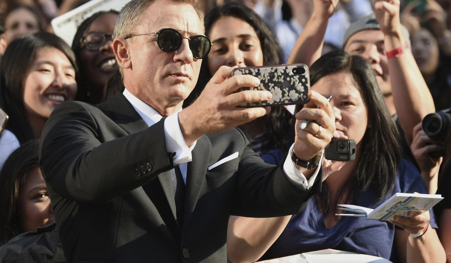 """Daniel Craig takes a selfie with fans as he attends the premiere for """"Knives Out"""" on day three of the Toronto International Film Festival at the Princess of Wales Theatre on Saturday, Sept. 7, 2019, in Toronto. (Photo by Evan Agostini/Invision/AP)"""