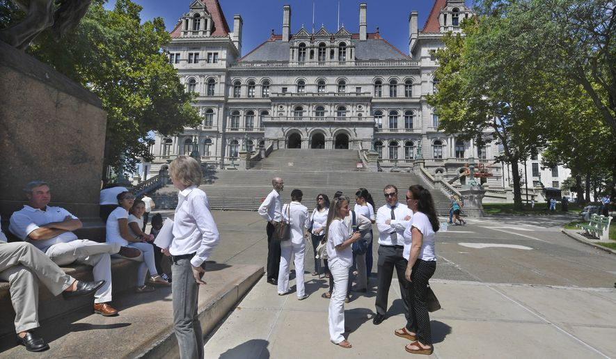 People wait outside the state Capitol after a hearing challenging the constitutionality of the state legislature's repeal of the religious exemption to vaccination after a rally outside the Albany County Courthouse Wednesday, Aug. 14, 2019, in Albany, N.Y. (AP Photo/Hans Pennink)