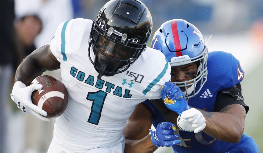 Coastal Carolina running back CJ Marable tries to run from a Kansas defender during an NCAA football game on Saturday, Sept. 7, 2019 in Lawrence, Kan. (AP Photo/Colin E. Braley) ** FILE **