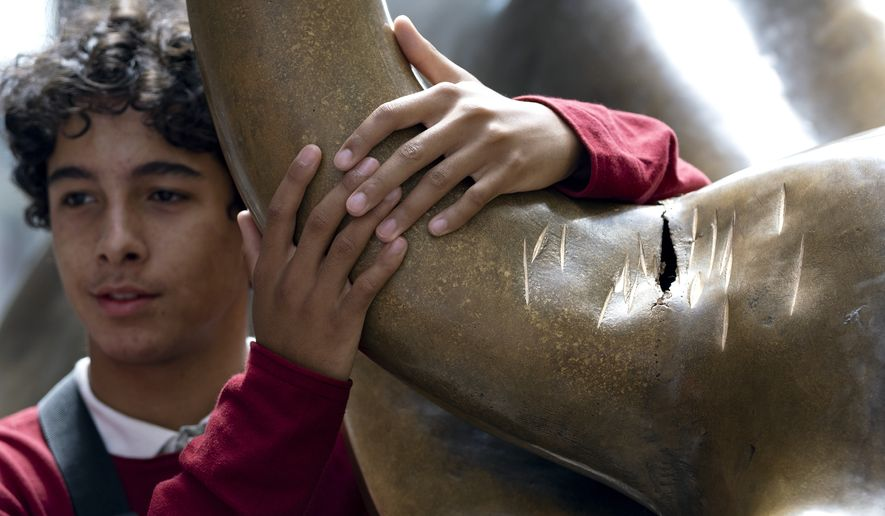 "A visitor poses next to the popular lower Manhattan sculpture ""Charging Bull,"" with a damaged right horn,  Sunday, Sept. 12, 2019, in New York. A man was arrested Saturday afternoon for damaging the iconic Wall Street Charging Bull statue with an object resembling a banjo, local media reported.  (AP Photo/Craig Ruttle)"