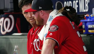 Washington Nationals pitcher Aaron Barrett ,right, talks with catcher Yan Gomes after pitching in his first major league game since 2015, in the fifth inning of a baseball game Saturday, Sept. 7, 2019, in Atlanta. (AP Photo/Tami Chappell)