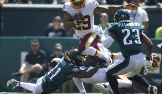 Washington Redskins running back Derrius Guice (29) jumps over Philadelphia Eagles cornerback Ronald Darby while carrying the football during an NFL football game, Sunday, Sept. 8, 2019, in Philadelphia, PA. (AP Photo/Jason E. Miczek) ** FILE **
