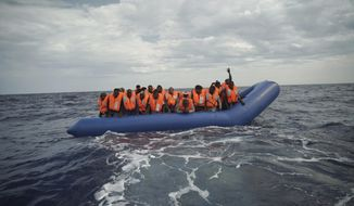 A migrant waves his hand in the air from on a blue rubber boat some 14 nautical miles from the coast of Libya in Mediterranean Sea, Sunday, Sept. 8, 2019. Humanitarian groups SOS Mediterranee and Doctors Without Borders have successfully rescued 50 migrants and brought them aboard the Ocean Viking. (AP Photo/Renata Brito)