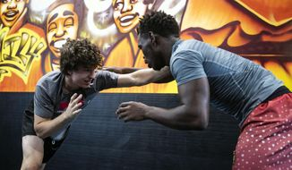 In this Aug. 17, 2019 photo, students pair up to start practicing takedown combinations at Stardust Jiu Jitsu in Memphis, Tenn. (Ariel Cobbert/The Commercial Appeal via AP)