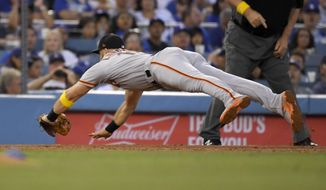 San Francisco Giants' Evan Longoria dives for a ground ball hit by Los Angeles Dodgers' Will Smith during the second inning of a baseball game Saturday, Sept. 7, 2019, in Los Angeles. Smith was safe at first on the play. (AP Photo/Mark J. Terrill)