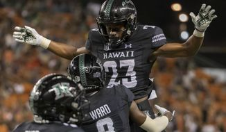 Hawaii wide receiver JoJo Ward (9) lifts his teammate wide receiver Jared Smart (23) celebrating his touch down reception during the second half of an NCAA college football game against Oregon State, Saturday, Sept. 7, 2019, in Honolulu. (AP Photo/Eugene Tanner)