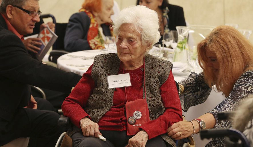 Janine Mazur, center, listens to speeches during an event to honor Polish people who saved Jews during WWII, in Warsaw, Poland, Sunday, Sept. 8, 2019. A U.S.-based Jewish foundation held an event in Warsaw on Sunday to honor Polish gentiles who rescued Jews during the Holocaust, a number that grows smaller each year, with U.S. and Israeli diplomats also paying their respects to the elderly Poles who put their lives in danger to save others. (AP Photo/Czarek Sokolowski)