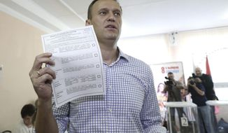 Russian opposition leader Alexei Navalny shows his ballot as he arrives to vote during a city council election in Moscow, Russia, Sunday, Sept. 8, 2019. Residents of Russia's capital are voting in a city council election that is shadowed by a wave of protests that saw the biggest demonstrator turnout in seven years and a notably violent police response. (AP Photo/Andrew Lubimov)