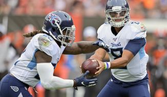 Tennessee Titans quarterback Marcus Mariota (8) hands off the ball to running back Derrick Henry (22) for a 1-yard touchdown during the first half in an NFL football game against the Cleveland Browns, Sunday, Sept. 8, 2019, in Cleveland. (AP Photo/David Richard)