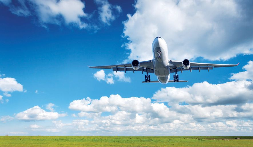 Beautiful airplane. Landscape with big white passenger airplane is flying in the blue sky with clouds over green grass field in summer. Passenger airplane is landing. Commercial plane. Aircraft