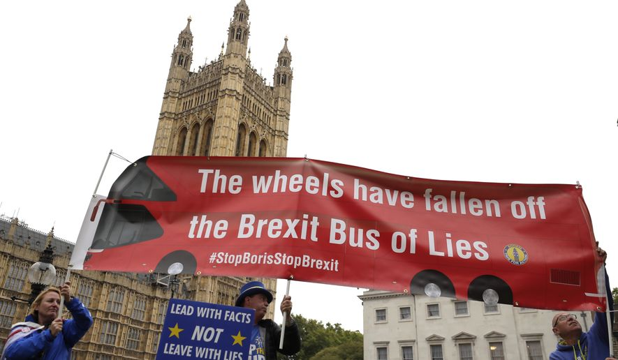 Anti-Brexit campaigner Steve Bray, centre, holds a banner near Parliament in London, Monday, Sept. 9, 2019. British Prime Minister Boris Johnson voiced optimism Monday that a new Brexit deal can be reached so Britain leaves the European Union by Oct. 31. (AP Photo/Kirsty Wigglesworth)