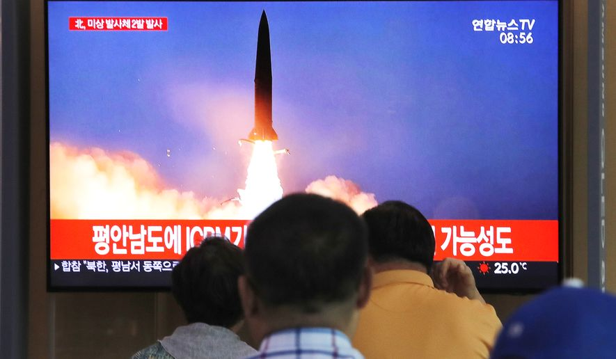 """People watch a TV showing a file image of a North Korea's missile launch during a news program at the Seoul Railway Station in Seoul, South Korea, Tuesday, Sept. 10, 2019. North Korea launched at least two unidentified projectiles toward the sea on Tuesday, South Korea's military said, hours after the North offered to resume nuclear diplomacy with the United States but warned its dealings with Washington may end without new U.S. proposals. The sign reads """"North Korea launched at least two unidentified projectiles."""" (AP Photo/Ahn Young-joon)"""