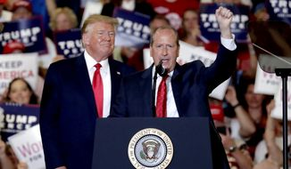 President Donald Trump, left, gives his support to Dan Bishop, right, a Republican running for the special North Carolina 9th District U.S. Congressional race as he speaks at a rally in Fayetteville, N.C., Monday, Sept. 9, 2019. (AP Photo/Chris Seward)