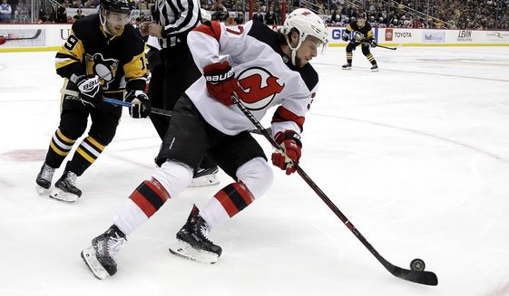 FILE - In this Jan. 28, 2019, file photo, New Jersey Devils' Pavel Zacha, center, skates during an NHL hockey game against the Pittsburgh Penguins in Pittsburgh, Monday, Jan. 28, 2019. Devils general manager Ray Shero says he is still attempting to sign Zacha amid concerns the former first-round draft pick will play in the Kontinental Hockey League this season. (AP Photo/Gene J. Puskar, File)