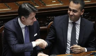 Italian Premier Giuseppe Conte shakes hands with Foreign Minister Luigi Di Maio after addressing parliament ahead of confidence vote later at the Lower Chamber in Rome, Monday, Sept. 9, 2019. The 5-Stars-PD alliance was the unexpected result of Italy's mid-summer crisis, which began when the League's Matteo Salvini, then the powerful interior minister and deputy premier, pulled the plug on the coalition hoping to trigger snap elections and win the premiership.(AP Photo/Andrew Medichini)