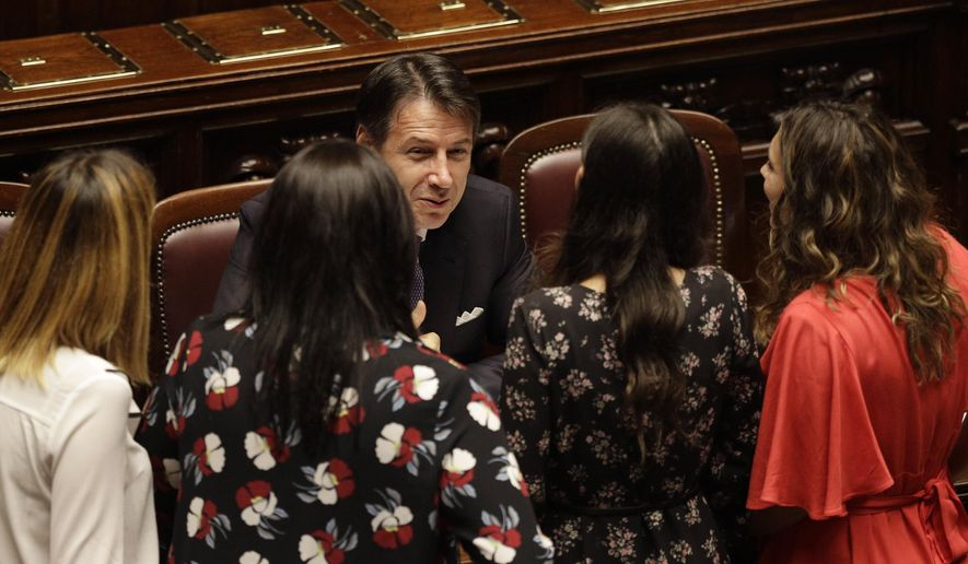 Italian Premier Giuseppe Conte, bottom center, talks with lawmakers during a confidence vote at the Lower Chamber in Rome, Monday, Sept. 9, 2019. Conte is pitching for support in Parliament for his new left-leaning coalition ahead of crucial confidence votes. (AP Photo/Gregorio Borgia)