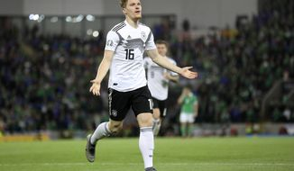 Germany's Marcel Halstenberg celebrates after scoring the opening goal during the Euro 2020 group C qualifying soccer match between Northern Ireland and Germany at Windsor Park, Belfast, Northern Ireland, Monday, Sept. 9, 2019. (AP Photo/Peter Morrison)