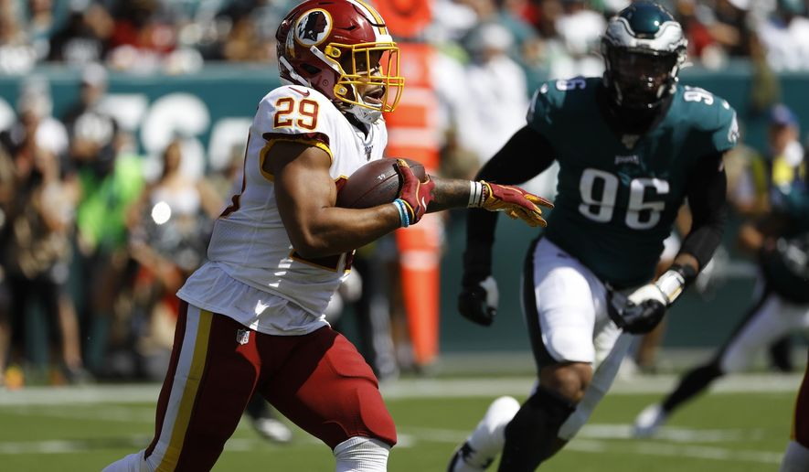 Washington Redskins' Derrius Guice, left, rushes during the first half of an NFL football game against the Philadelphia Eagles, Sunday, Sept. 8, 2019, in Philadelphia. (AP Photo/Michael Perez)
