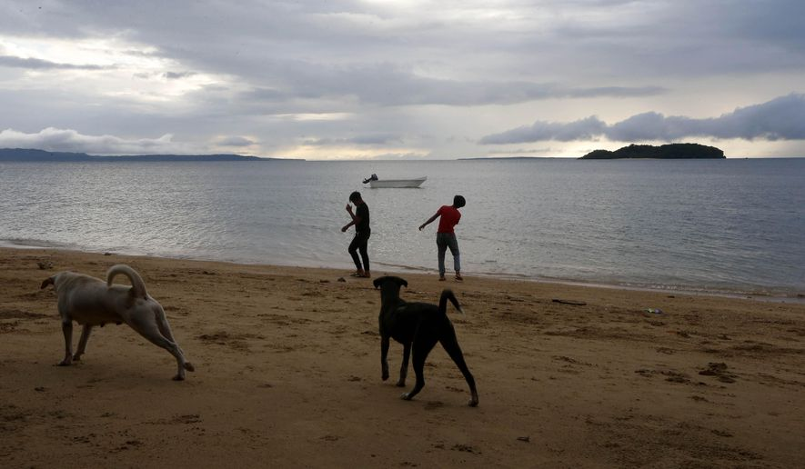 In this Jan. 27, 2019 photo, two boys play by the shore at a beach resort in Talustusan on Biliran Island in the central Philippines. Since Decmeber 2018, the small village has been rocked by controversy after about 20 boys and men, including these two, accused their Catholic parish priest Father Pius Hendricks of years of alleged sexually abuse. (AP Photo/Bullit Marquez)