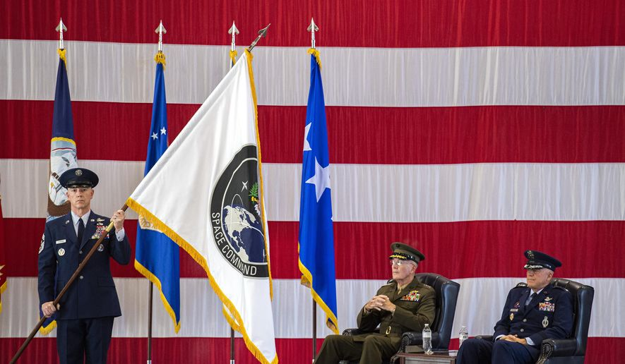 In this file photo from Sept. 9, 2019, Gen. John W. Raymond, U.S. Air Force and commander of the U.S. Space Command, right, and Gen. Joseph F. Dunford, Jr., U.S. Marines and Chairman of the Joint Chiefs of Staff, watch during the presentation of the new U.S. Space Command colors during a ceremony to recognize the establishment of the United States Space Command at Peterson Air Force Base in Colorado Springs, Colo. (Christian Murdock/The Gazette via AP) **FILE**