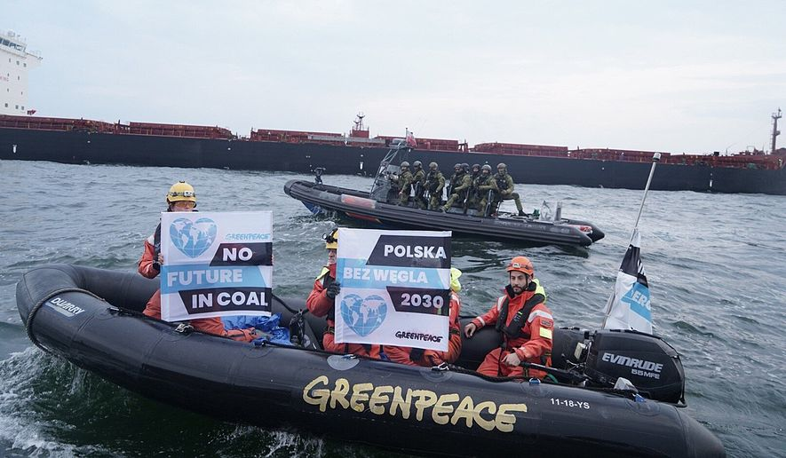 In this Monday, Sept. 9, 2019, photo provided by the environment group Greenpeace, activists of Greenpeace are seen in a boat with anti-coal slogans, trying to block a cargo ship with coal from Mozambique to enter the port in Gdansk, Poland. Armed and masked Polish border guards boarded a Greenpeace ship and briefly detained 22 activists onboard. The ship's Spanish captain and an Austrian activist remain under detention. (Greenpeace via AP) ** FILE **