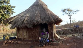 Mary Chipiro, a farm worker at Former Zimbabwean President Robert Mugabe's Dairy farm, sits with her child outside her thatched hut at the farm compound in Mazoe, Zimbabwe, Monday, Sept, 9 2019. Mugabe, who enjoyed strong backing from Zimbabwe's people after taking over in 1980, but whose support waned following decades of repression, economic mismanagement and allegations of election-rigging, is expected to be buried on Sunday, state media reported. (AP Photo/Tsvangirayi Mukwazhi)