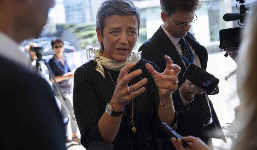 European Commissioner for Competition Margrethe Vestager talks to journalists outside of the EU headquarters in Brussels, Tuesday, Sept. 10, 2019. The incoming president of the European Union's powerful executive arm nominated Denmark's Margrethe Vestager to the position of EU Commissioner for a Europe Fit For the Digital Age. (AP Photo/Francisco Seco)