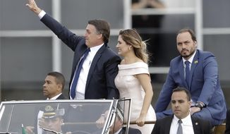 FILE - In this Jan 1, 2019 file photo, flanked by first lady Michelle Bolsonaro, center, and his son Carlos Bolsonaro, right, Brazil's President Jair Bolsonaro waves as he rides in an open car after his swearing-in ceremony, in Brasilia, Brazil. Carlos Bolsonaro's tweet on Monday, Sept. 10,  has caused an uproar saying democracy is slowing development in Latin America's biggest country. (AP Photo/Andre Penner, File)