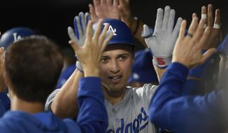 Los Angeles Dodgers' Corey Seager is congratulated in the dugout for his three-run home run during the first inning of the team's baseball game against the Baltimore Orioles, Tuesday, Sept. 10, 2019, in Baltimore. (AP Photo/Nick Wass)