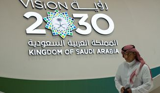 "A Saudi man walks past a ""Vision 2030"" display at a stand about Saudi Arabia during the World Energy Congress in Abu Dhabi, United Arab Emirates, Tuesday, Sept. 10, 2019. Amin Nasser, the chairman and CEO of the state-run oil giant Saudi Aramco, told journalists Tuesday a planned initial public offering of a sliver of the company's worth would happen ""very soon."" ""Vision 2030"" is an ambitious plan by Saudi Arabia's Crown Prince Mohammed bin Salman that includes the IPO of a small part of Saudi Aramco to help fund its efforts. (AP Photo/Jon Gambrell)"