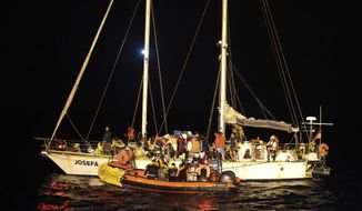 Migrants are transferred onto a dinghy from a 14-meter sailboat Josefa, run by the group Resqship, after being rescued near the Bouri Oil Fields, to be taken onto the humanitarian ship Ocean Viking, in the Mediterranean Sea, late Monday, Sept. 9, 2019. Thirty-four migrants including women and the small child who were rescued by the German sailboat have been successfully taken aboard the humanitarian ship in international waters north of Libya despite a thunderstorm. (AP Photo/Renata Brito)