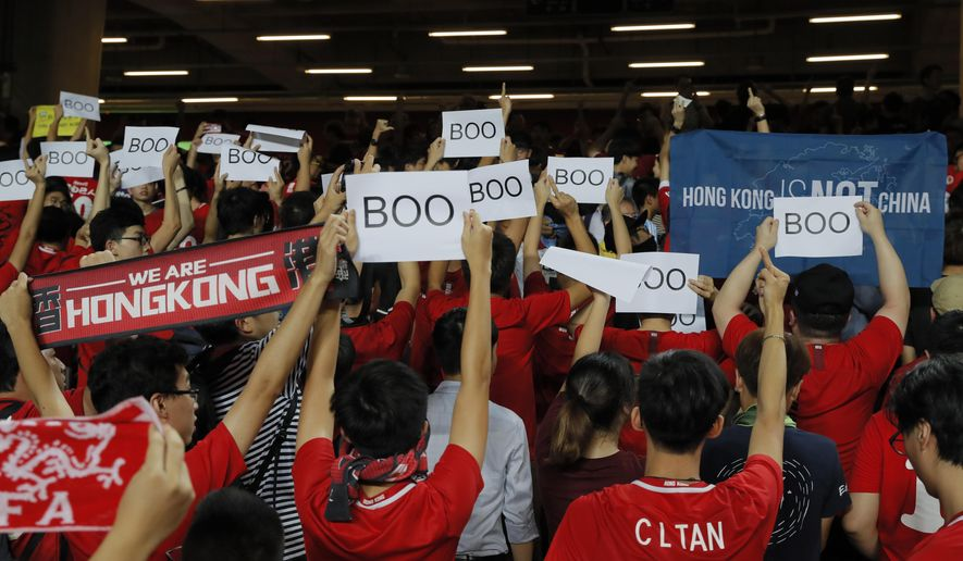 """Hong Kong soccer fans turn their back and boo the Chinese national anthem as they chant """"Hong Kong is not China"""" during the FIFA World Cup Qatar 2022 and AFC Asian Cup 2023 Preliminary Joint Qualification Round 2 soccer match between Hong Kong and Iran, in Hong Kong, Tuesday, Sept. 10, 2019. The crowd broke out into """"Glory to Hong Kong,"""" a song reflecting their campaign for more democratic freedoms in the semi-autonomous Chinese territory. (AP Photo/Kin Cheung)"""