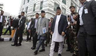 Prime Minister Khadga Prasad Oli, center right, leaves after virtually inaugurating the Nepal-India cross border petroleum pipeline through video conference in Kathmandu, Nepal, Tuesday, Sept. 10, 2019. Indian Prime Minister Narendra Modi and Oli hit the switch simultaneously Tuesday from their offices in New Delhi and Kathmandu to open the 69-kilometer (43-mile) pipeline, which will bring gasoline, diesel fuel and kerosene across the border to Nepal. (AP Photo/Bikram Rai)