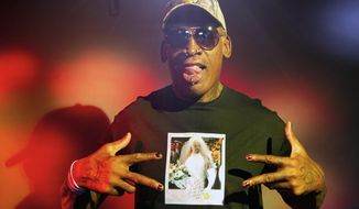 "In this Monday, Sept. 9, 2019, photo, former NBA star Dennis Rodman poses wearing a T-shirt depicting himself in a wedding dress at a 1996 book promo event, in Los Angeles. After a career of spectacular highs and very public lows, Dennis Rodman keeps finding new ways to surprise. The former NBA star, featured in a new ESPN documentary, weighs in on his personal brand, bisexual athletes, North Korea and Trump. Rodman's spectacular personal highs and very public lows are the subject of the new ESPN ""30 For 30"" documentary ""Dennis Rodman: For Better or Worse.""  (AP Photo/Damian Dovarganes)"