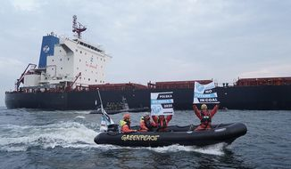 In this Monday, Sept. 9, 2019 photo provided by the environment group Greenpeace activists of Greenpeace are seen in boats with anti-coal slogans, trying to block a cargo ship with coal from Mozambique to enter the port in Gdansk, Poland. Armed and masked Polish border guards boarded a Greenpeace ship and briefly detained 22 activists onboard. The ship's Spanish captain and an Austrian activist remain under detention. (Greenpeace via AP)