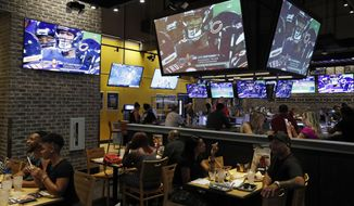 People eat and watch football at a Buffalo Wild Wings, Thursday, Sept. 5, 2019, in Las Vegas. MGM Resorts International and Buffalo Wild Wings are launching a mobile football game app for customers to pick favorite NFL teams, choose weekly fantasy performers and make proposition picks. Officials said the goal is to expand later at Buffalo Wild Wings in states where sports betting is legal through a mobile app called BetMGM. (AP Photo/John Locher)