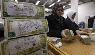 FILE - This January 13, 2010 file photo, employees stack Syrian currency in the Central Bank, in Damascus, Syria. The Syrian pound has crashed to its lowest levels in recent days against the U.S. dollar leading to increase in prices in the war-torn country. The pound was trading Tuesday, Sept. 10, 2019, at 660 to the dollar after it reached last week 690 pounds on the black market, a figure never reached before. (AP Photo/Hussein Malla, File)