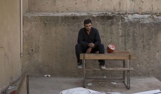 In this Saturday, Sept. 7, 2019, photo, a first responders takes a break after removing a body at the site of a mass grave in Raqqa, Syria. First responders say they have pulled nearly 20 bodies out of the latest mass grave uncovered in Raqqa, the Syrian city that was the de facto capital of the Islamic State group. It is the 16th mass grave in the city, and officials are struggling with a lack of resources needed to document and one day identify the thousands of dead who have been dug out. (AP Photo/Maya Alleruzzo)