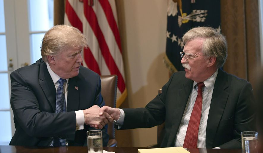 In this April 9, 2018 file photo, President Donald Trump, left, shakes hands with national security adviser John Bolton in the Cabinet Room of the White House in Washington at the start of a meeting with military leaders.  Trump has fired national security adviser John Bolton. (AP Photo/Susan Walsh)