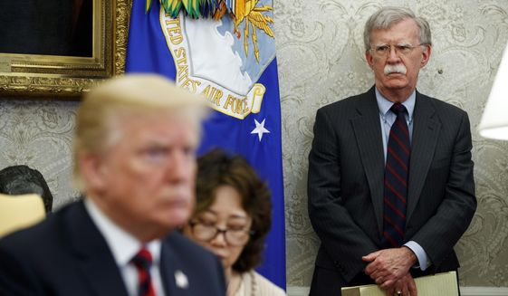In this May 22, 2018, file photo, U.S. President Donald Trump, left, meets with South Korean President Moon Jae-In in the Oval Office of the White House in Washington, as then-National Security Adviser John Bolton, right, watches. (AP Photo/Evan Vucci, File)