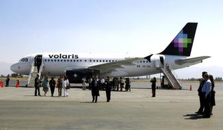 FILE - In this March 13, 2006 file photo, visitors observe a Volaris airplane at the Ciudad de Toluca airport, in Mexico. Documents show the city of Albuquerque, N.M., spent nearly $1.6 million to promote the Mexico-based airline that had promised, then canceled, regular international flights in July 2019. (AP Photo/Claudio Cruz, File)
