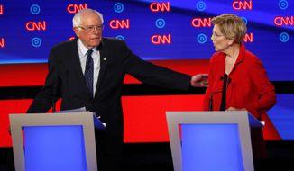 """Part of a """"liberal sandwich""""? Sen. Bernard Sanders and Sen. Elizabeth Warren share a moment at a Democratic presidential debate in Detroit. (Associated Press)"""