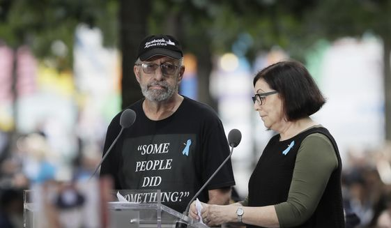 Nic Haros, left, participates in a ceremony marking the 18th anniversary of the attacks of Sept. 11, 2001 at the National September 11 Memorial, Wednesday, Sept. 11, 2019 in New York. Haros read a statement during the ceremony addressed to U.S. Rep. Ilhan Omar, D-Minn. (AP Photo/Mark Lennihan)