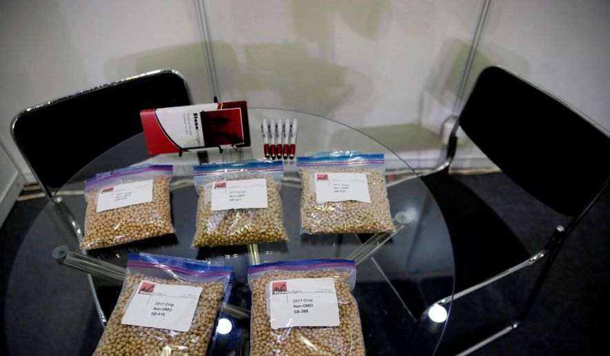 In this April 12, 2018, file photo, packets of raw soybeans are placed on a table at a U.S. soybean company's booth at the international soybean exhibition in Shanghai, China. China has announced some U.S. industrial chemicals will be exempt from tariff hikes imposed in a trade war with Washington but maintained penalties on soybeans, pork and other farm goods. The Ministry of Finance's announcement Wednesday, Sept. 11, 2019, came ahead of October talks aimed at ending the fight over trade and technology that threatens global economic growth. (AP Photo/Andy Wong, File)